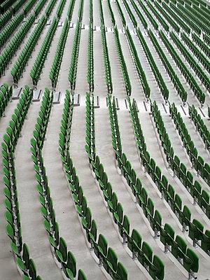 Rows of empty seats inside sports stadium - p1072m2151278 by Neville Mountford-Hoare