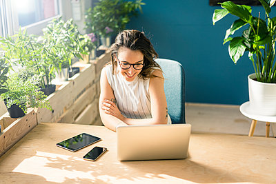 Smiling freelancer sitting at desk in loft looking at laptop - p300m1581100 by Robijn Page