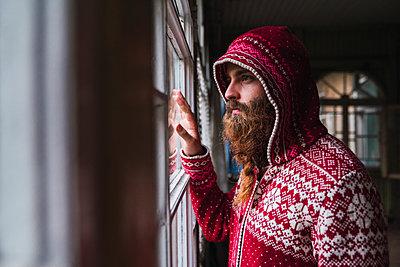 Portrait of pensive man with beard wearing hooded jacket looking out of window - p300m2060877 von Kike Arnaiz