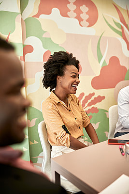 Businesswoman smiling during meeting at desk in coworking office - p300m2282724 by Zeljko Dangubic