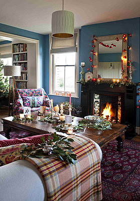 Lit fire and fairy lights with wooden coffee table in country home at Christmas - p349m790827 by Polly Eltes