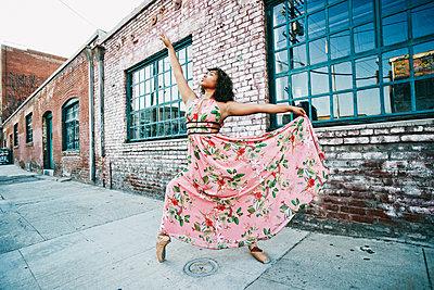 Mixed race ballet dancer wearing dress on sidewalk - p555m1521632 by Peathegee Inc