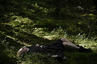 Shadows on Caucasian woman laying in grass - p555m1531603 by Ivan Ozerov