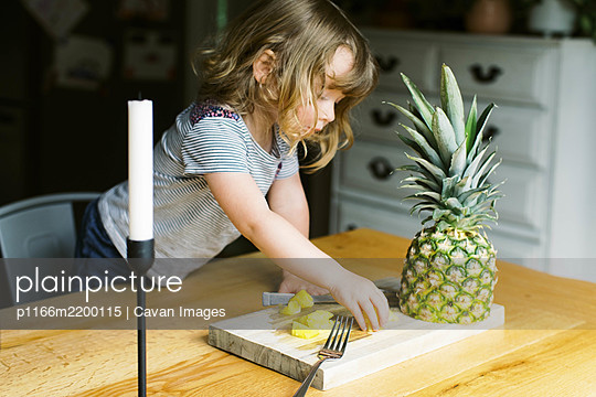 A little toddler girl having a healthy pineapple snack - p1166m2200115 by Cavan Images