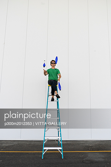 Acrobat wearing sunglasses, sitting on ladder, juggling - p300m2012353 von VITTA GALLERY