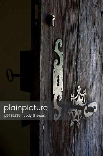 Detail of wooden door with ornate ironwork door furniture - p3493293 by Jody Stewart