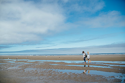 Side view of girls walking on shore at beach against sky - p1166m1524545 by Cavan Images