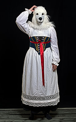 Woman in traditional costume and dog mask - p1366m2260589 by anne schubert