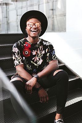 Portrait of laughing man wearing hat, sunglasses and black t-shirt with floral design sitting on stairs - p300m1549521 by Oriol Castelló Arroyo