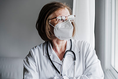 Senior female doctor with protective face mask looking away while standing in hospital - p300m2274465 by Eva Blanco