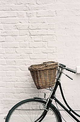Bicycle propped up against a white brick wall - p349m695134 by Emma Lee
