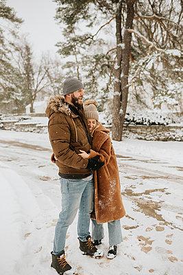 Canada, Ontario, Hugging couple standing on snowy road - p924m2271216 by Sara Monika