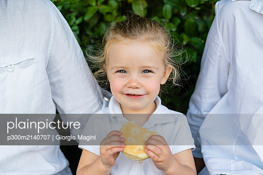 Portrait of little girl with a snack sitting amidst parents - p300m2140707 by Giorgio Magini