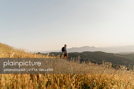 Active senior man looking at landscape while standing on mountain - p300m2202425 by VITTA GALLERY