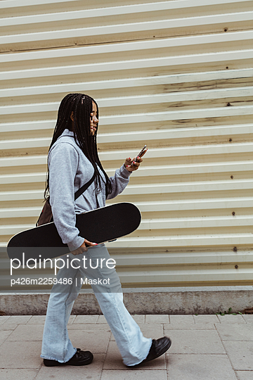 Teenage girl with skateboard using smart phone while walking on footpath by metal wall - p426m2259486 by Maskot