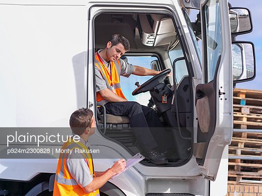 UK, Truck driver and supervisor checking paperwork - p924m2300828 by Monty Rakusen