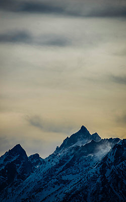 Low angle view of snowcapped mountain against cloudy sky during sunset at Grand Teton National Park - p1166m1417515 by Cavan Images