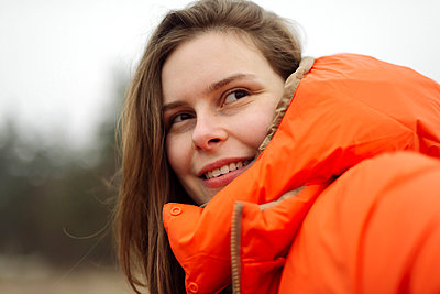 Portrait of young woman smiling outdoors - p1166m2162709 by Cavan Images