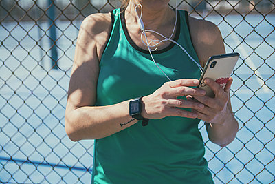 Athlete woman listening to music from her mobile phone - p1166m2171649 by Cavan Images
