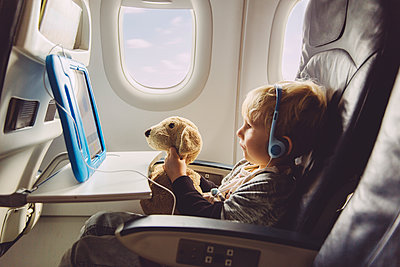 Little boy sitting on an airplane watching something on digital tablet - p300m1188313 by Mareen Fischinger