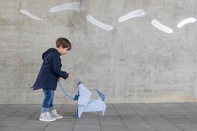 Little boy exercising with origami dog - p300m2012945 von Petra Stockhausen