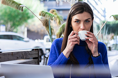 Woman with gray eyes drinking coffee in sidewalk cafe - p300m2257152 by NOVELLIMAGE