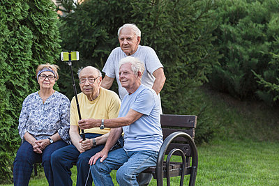 Smiling senior friends taking selfie by using monopod at park bench - p301m1180615 by Vladimir Godnik
