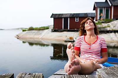 A woman sitting on a jetty in the archipelago of Stockholm Sweden. - p31220502f by Plattform