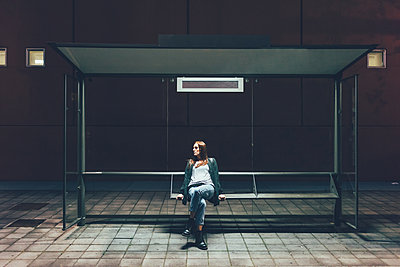 Young woman sitting at bus stop at night - p429m1197810 by Eugenio Marongiu
