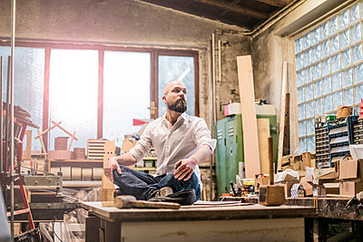 Carpenter in workshop sits on table - p586m1496245 by Kniel Synnatzschke