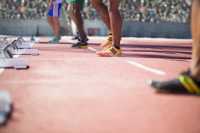 Runners standing at starting blocks on track - p1023m923559f by Paul Bradbury