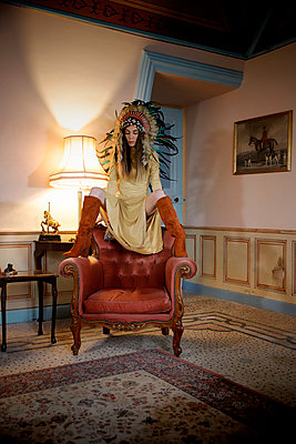 Woman with indian headdress in an armchair, portrait - p1105m2245467 by Virginie Plauchut