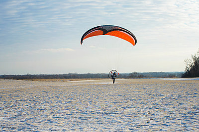 Young man motor paragliding over field against sky - p1166m1531544 by Cavan Images