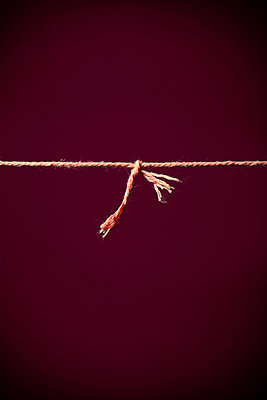 Taut string with knot against red background - p1248m2278939 by miguel sobreira