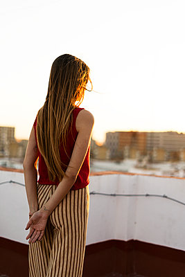 Rear view of teenage girl standing on roof terrace in the city at sunset - p300m2103177 by Eloisa Ramos