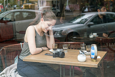 Young woman using smartphone in cafe - p429m2077838 by Tamboly