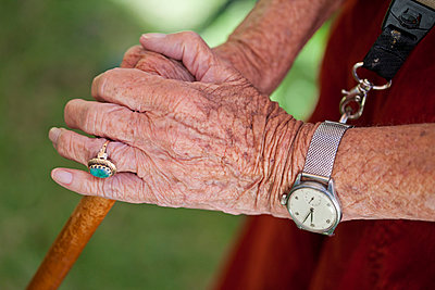 Close up of senior woman's hands holding walking stick - p429m911588f by Zero Creatives
