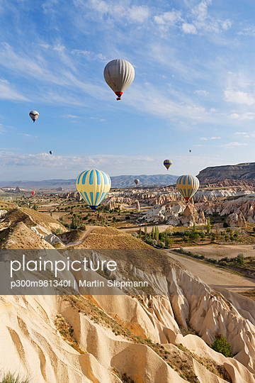 Turkey, Cappadocia, hot air balloons hoovering over tuff rock formations at Goereme National Park - p300m981340f by Martin Siepmann