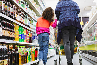 Mother and daughter shopping in supermarket - p1023m2187673 by Sam Edwards