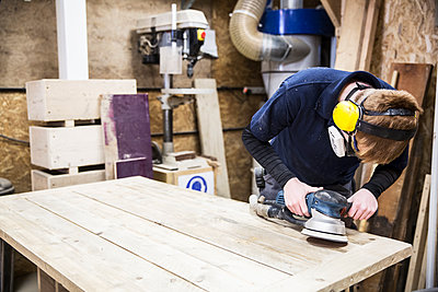 Man wearing ear protectors, protective goggles and dust mask standing in a warehouse, using sander to smoothen piece of wood. - p1100m1575722 by Mint Images