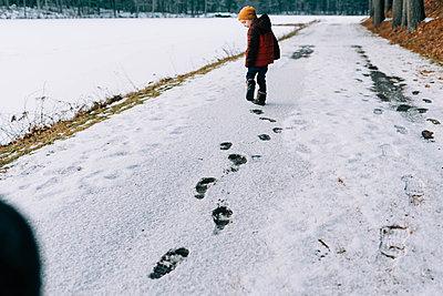 Little boy looking at the footprints he is leaving behind in the snow. - p1166m2157324 by Cavan Images