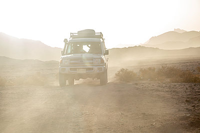 Off-road vehicle on dirt road amidst dust in desert against sky during sunset - p300m2132361 by Nadine Ginzel