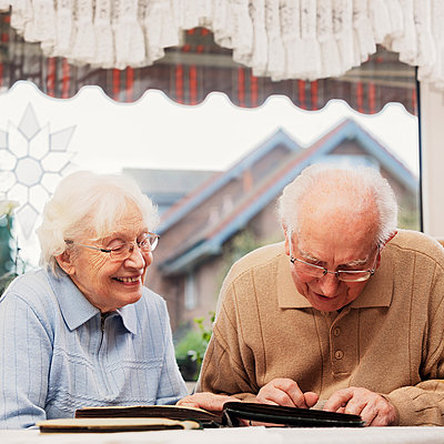 Senior couple watching old photographs at home - p300m884966f by Ingo Bartussek