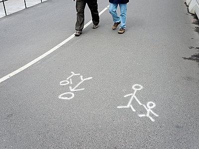 Stick figures on asphalt road - p312m1550614 by Johner
