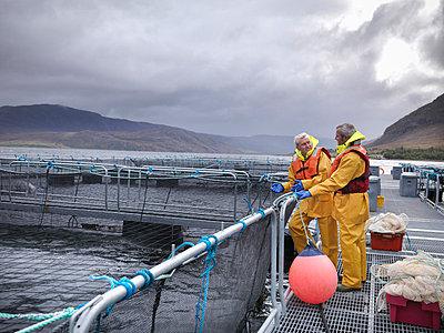 Workers talking at fish farm - p42917326f by Monty Rakusen