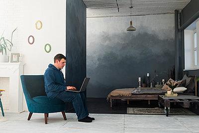 Caucasian man sitting in chair using laptop - p555m1444045 by Aleksander Rubtsov