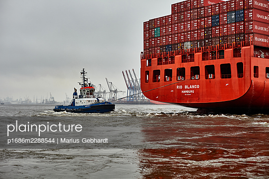Container ship and tugboat - p1686m2288544 by Marius Gebhardt