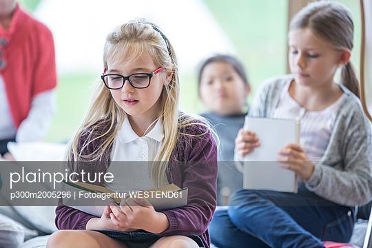 Schoolgirls reading books in school break room - p300m2005296 von Fotoagentur WESTEND61