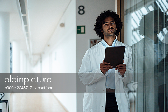 Thoughtful young male doctor holding digital tablet while leaning on glass wall at hospital corridor - p300m2243717 by Joseffson