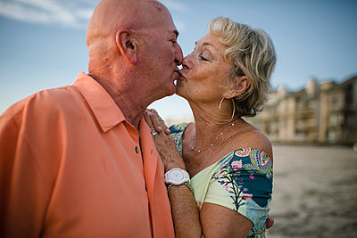 Romantic senior couple kissing while standing at beach against sky - p1166m1531320 by Cavan Images